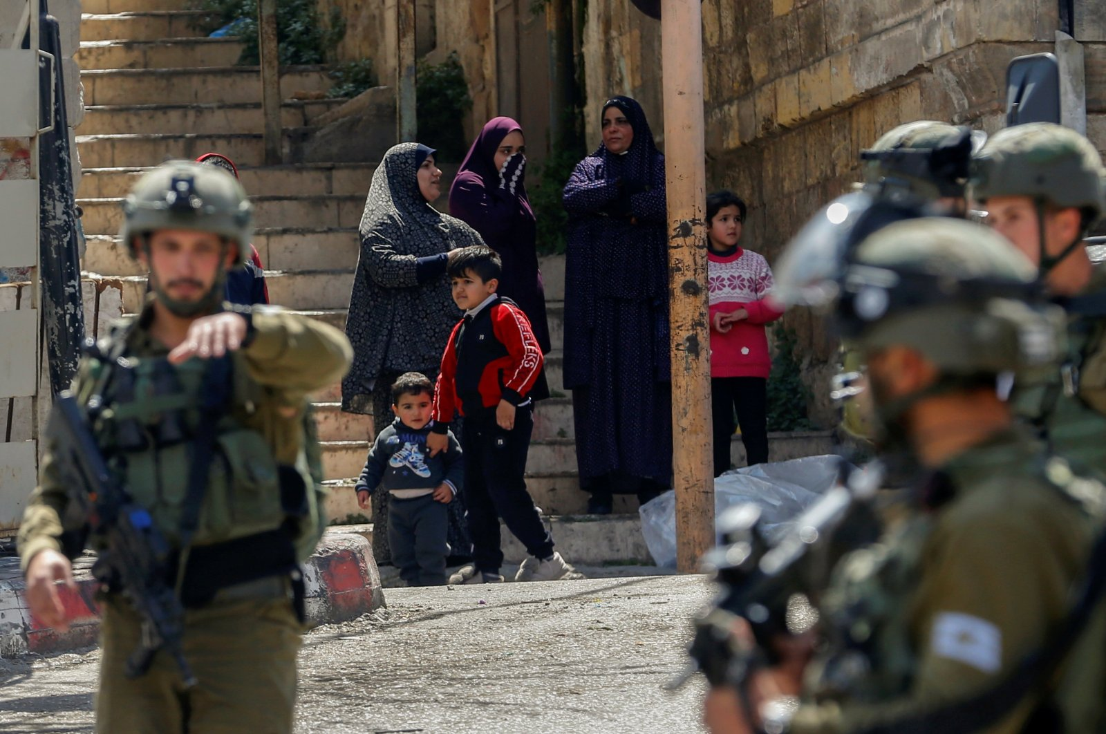Palestinians watch as Israeli soldiers stand guard during a protest against visits by Israeli settlers, in Hebron in the Israeli-occupied West Bank, March 31, 2021. (Reuters Photo)