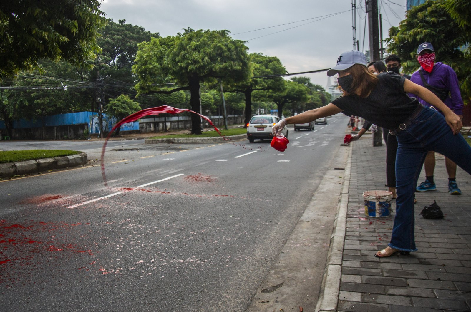 Anti-coup protesters throw red paint on a street during a demonstration in Yangon, Myanmar, April 6, 2021. (AP Photo)