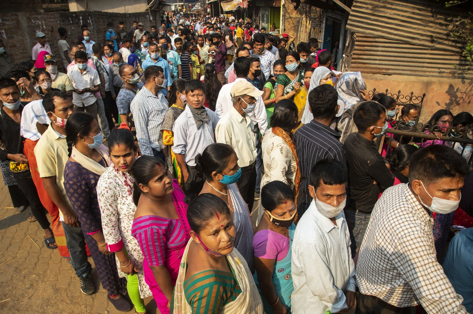 People stand in line to cast their votes in a polling station during the third phase of the assembly election in Gauhati, India, April 6, 2021. (AP Photo)
