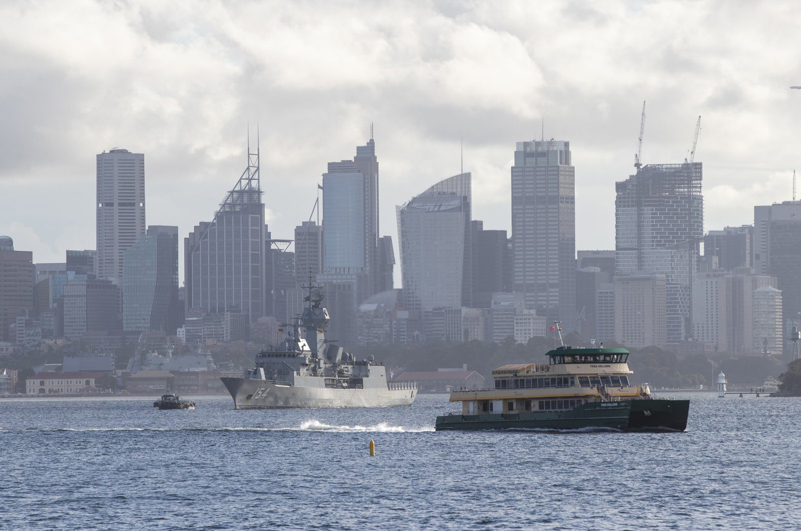 A ferry sails across the Sydney harbor past the HMAS Arunta, an Anzac-class frigate of the Royal Australian Navy, moored in Sydney, Australia, April 6, 2021.