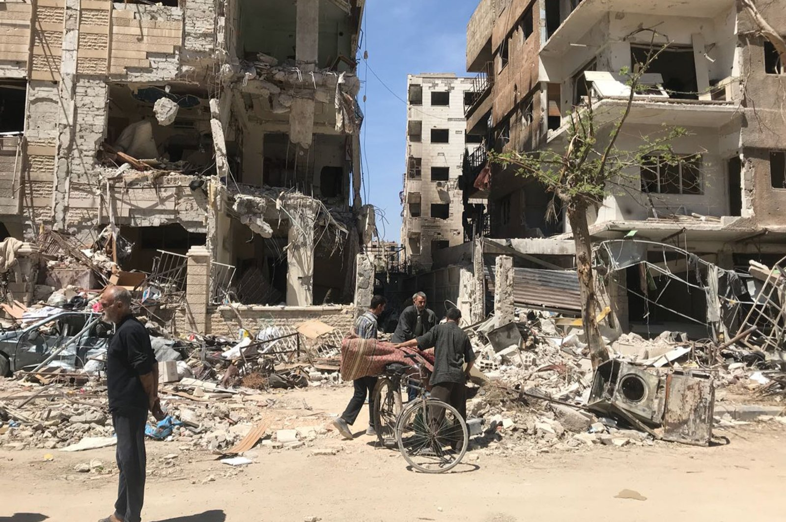 People stand in front of damaged buildings, in the town of Douma, the site of a chemical weapons attack, near Damascus, Syria, Monday, April 16, 2018. (AP Photo/Hassan Ammar)