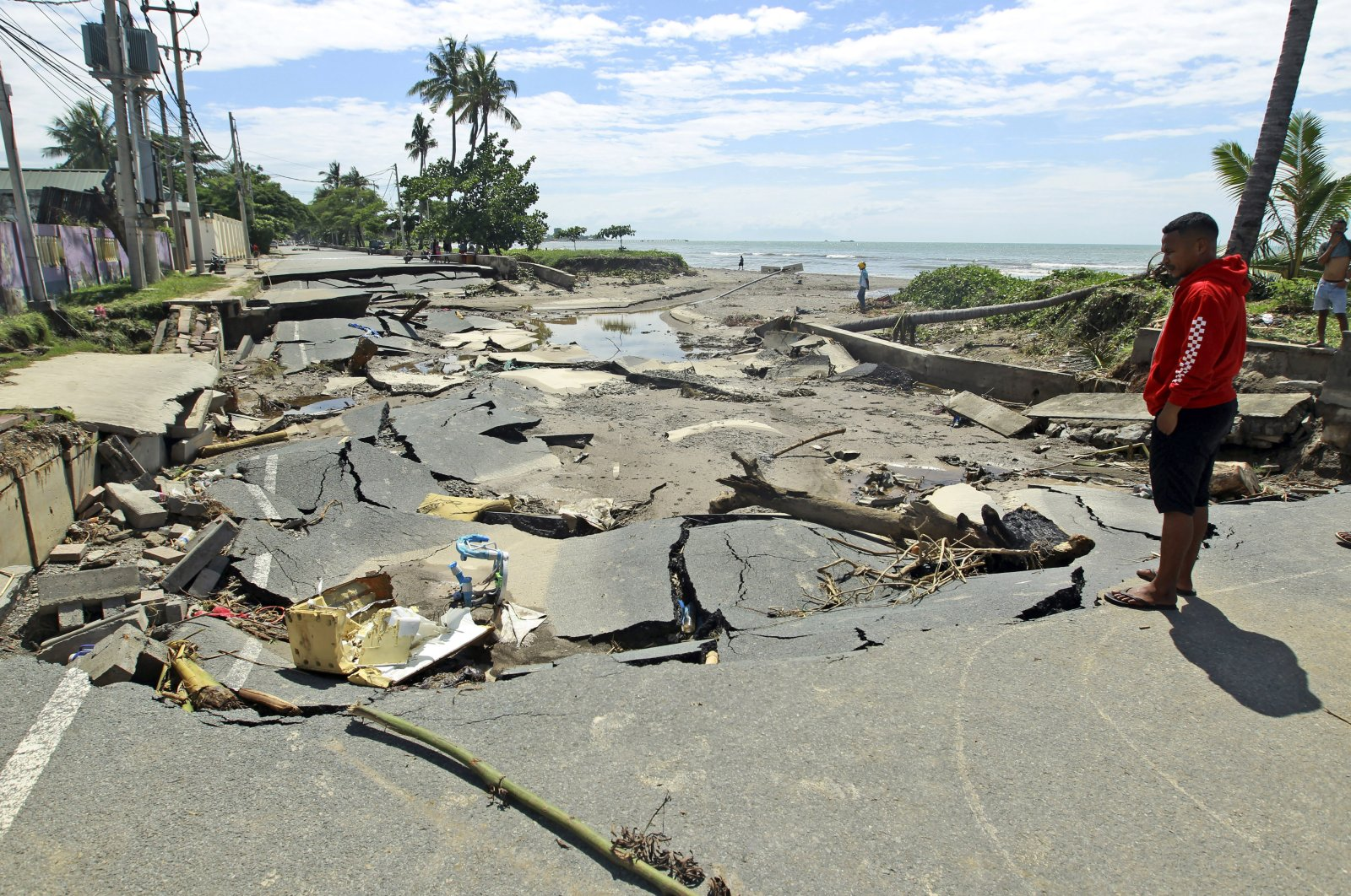 A man inspects a road destroyed after a flood in Dili, East Timor, April 6, 2021. (AP Photo)