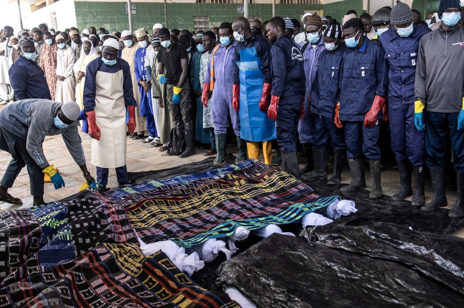 Volunteers of the Association For Solidarity and Perfection (JRWI) cover the 28 unidentified corpses which are laid out at a mosque ahead of a prayer in Dakar, Senegal, March 28, 2021. (AFP Photo)