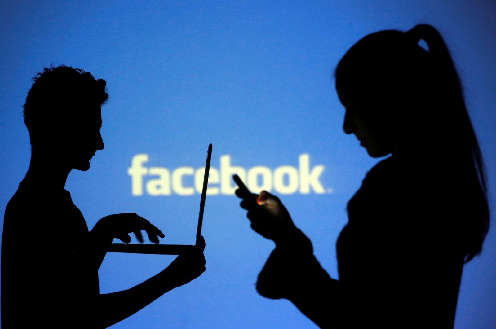 People are silhouetted as they pose with laptops in front of a screen projected with a Facebook logo, in this picture illustration, Oct. 29, 2014. (Reuters Photo)