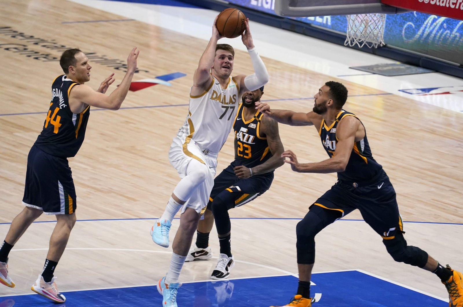 Dallas Mavericks guard Luka Doncic (C) leaps to the basket for a shot as Utah Jazz's Bojan Bogdanovic (L), Royce O'Neale and Rudy Gobert (R) defend in an NBA game in Dallas, U.S., April 5, 2021. (AP Photo/Tony Gutierrez)