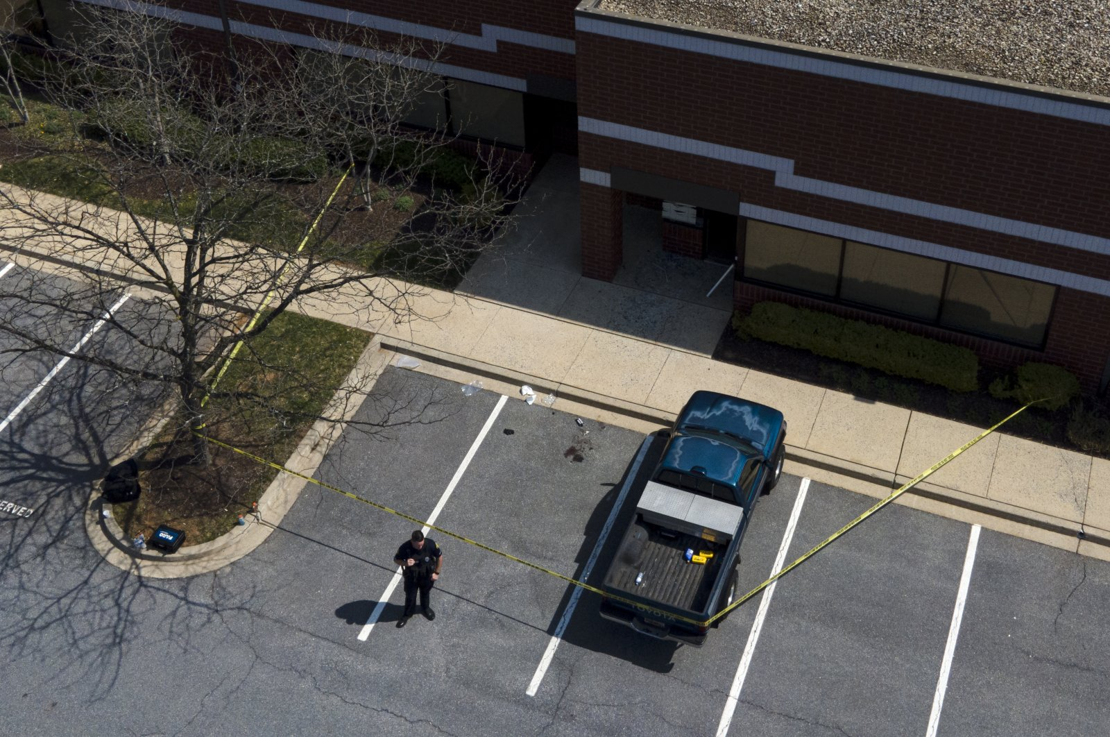An official stands near a taped-off area near the scene of a shooting at a business park in Frederick, Maryland, U.S., April 6, 2021. (AP Photo)