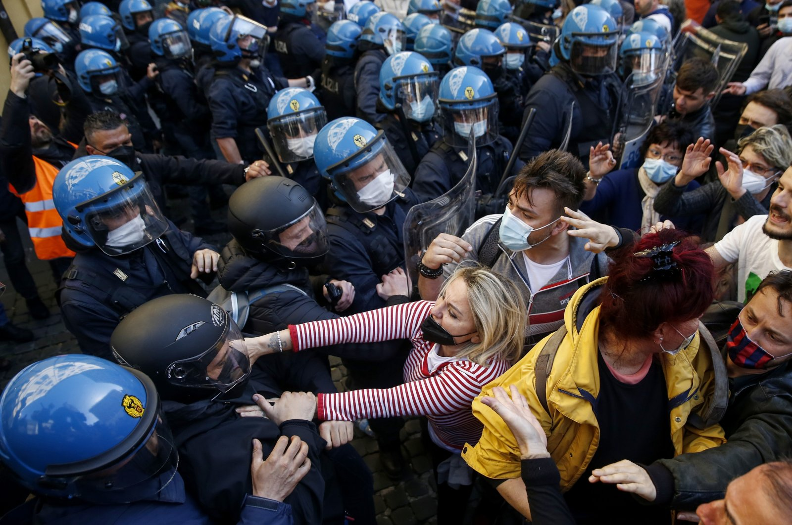 Demonstrators scuffle wit Italian Policemen in riot gear outside the lower Chamber during a protest by restaurant and other business activity owners in Rome, Tuesday, April 6, 2021.  (Lapresse Via AP)