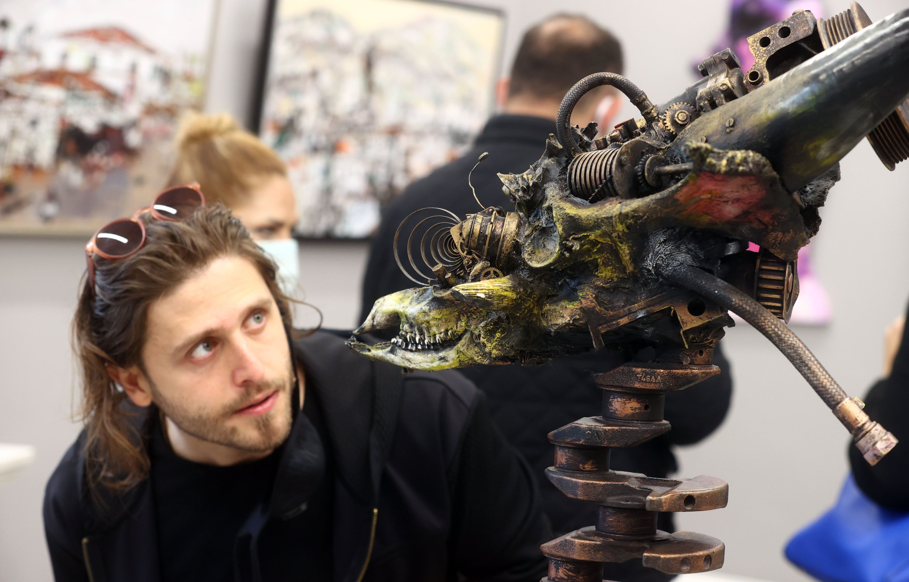 A visitor examines a post-apocalyptic sculpture by Uğur Çalışkan at an exhibition in this photo provided on April 6, 2021. (AA Photo)