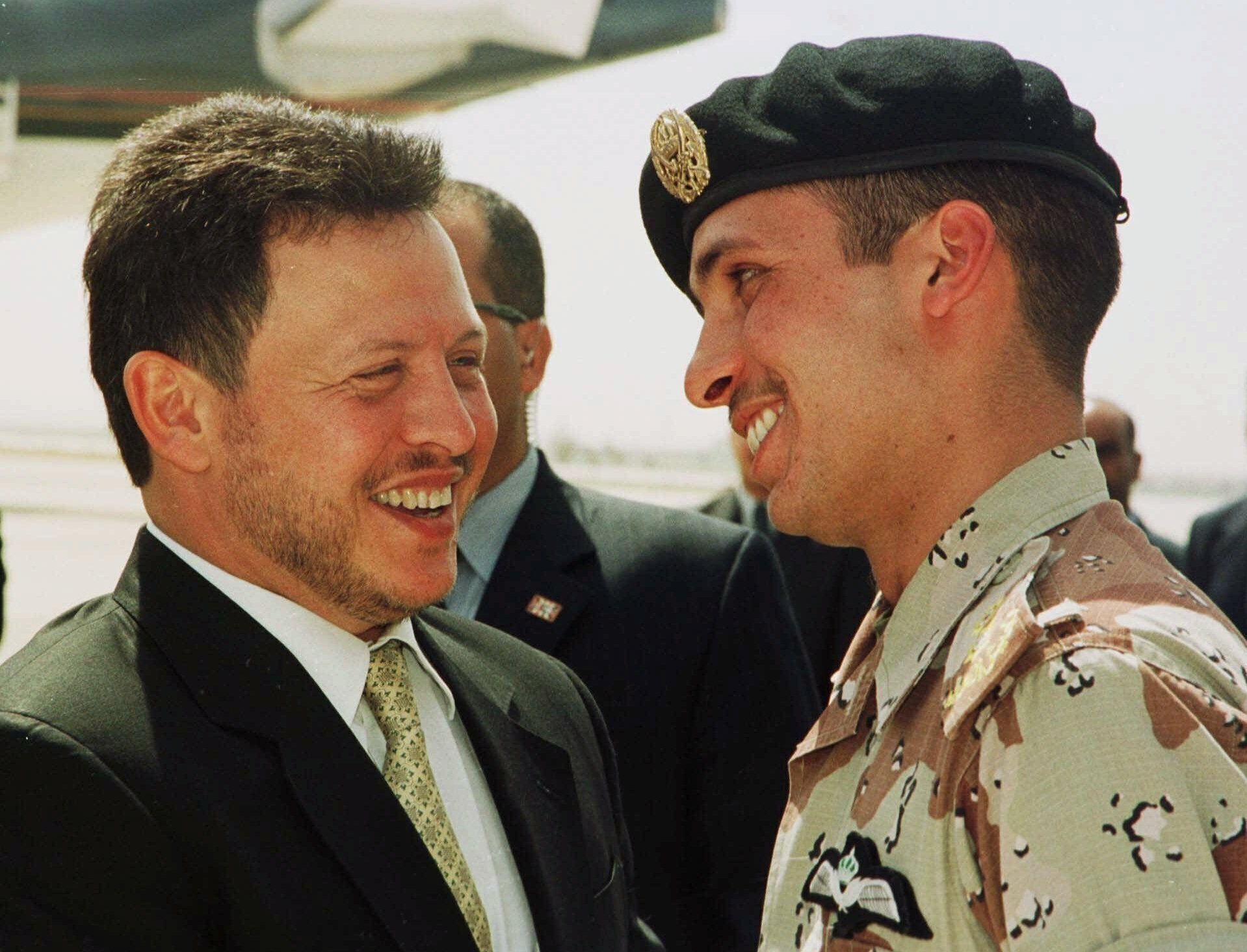 Jordan's King Abdullah II laughs with his half-brother Prince Hamzah (R) shortly before the monarch embarked on a tour of the United States, Jordan, April 2, 2001. (AP Photo)