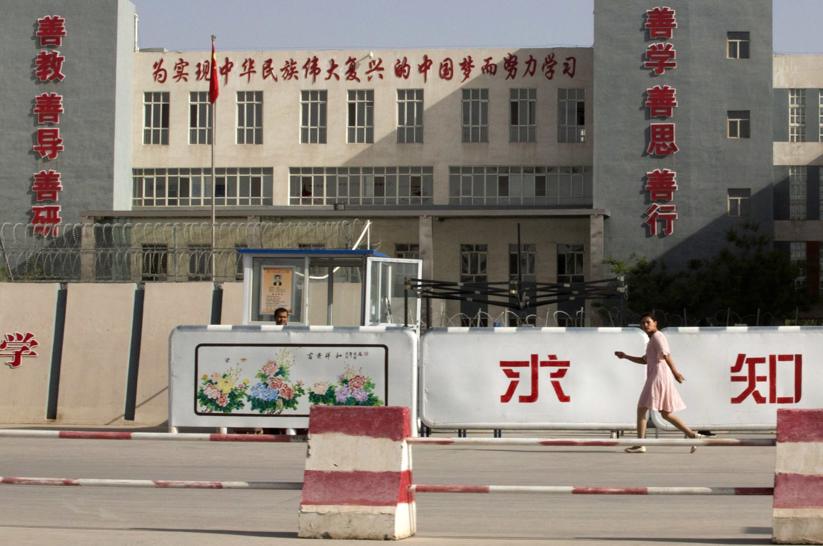 """A woman walks past the Kashgar Dongcheng No. 4 Junior Middle School, which is part of a cluster of schools with slogans that read, """"Study hard to realize the Chinese dream of the great rejuvenation of the Chinese nation,"""" on the outskirts of Kashgar, in the Xinjiang Uyghur Autonomous Region, western China, Aug. 31, 2018. (AP Photo)"""