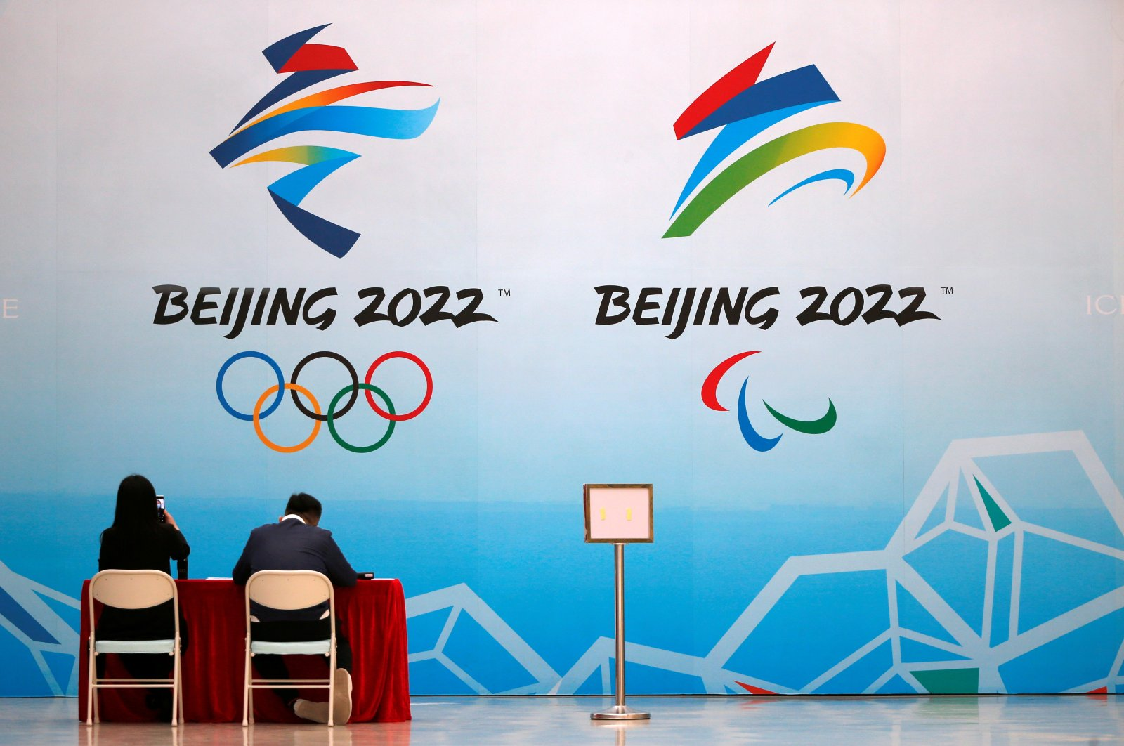 """Staff members sit near a board with signs of the 2022 Olympic Winter Games, at the National Aquatics Center, known colloquially as the """"Ice Cube,"""" in Beijing, China, April 1, 2021. (Reuters Photo)"""