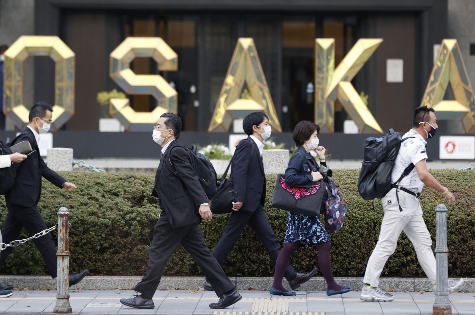 People wearing face masks to help curb the spread of the coronavirus walk in Osaka, western Japan, Friday, April 2, 2021. (AP Photo)