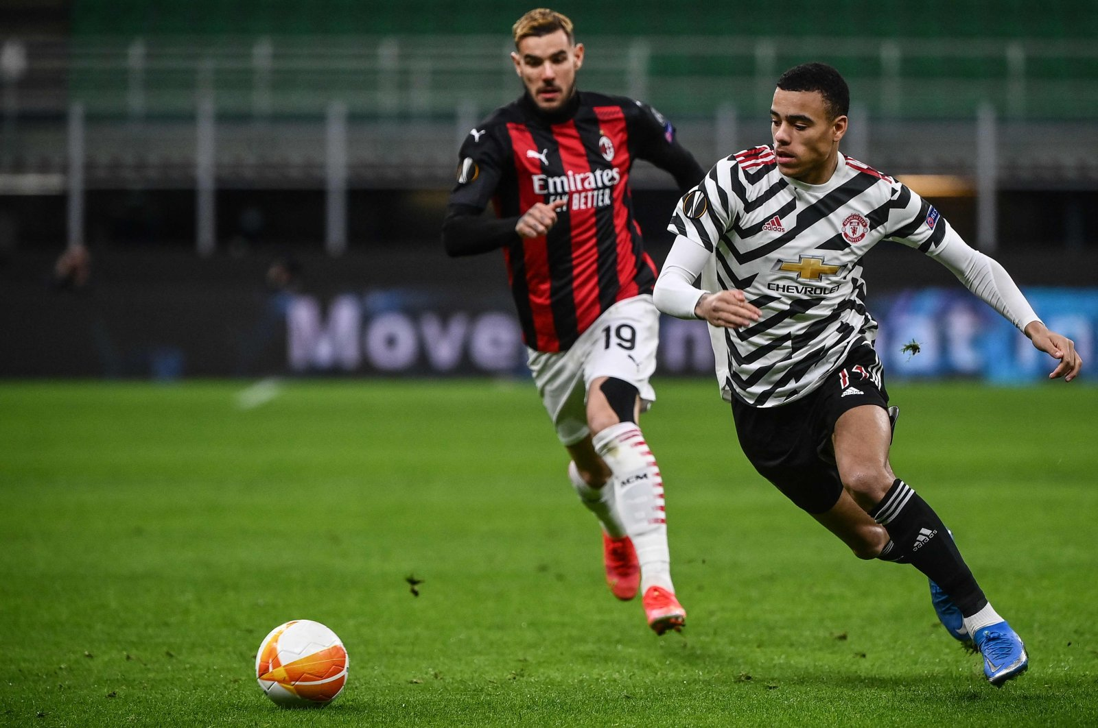 Manchester United forward Mason Greenwood (R) outflanks AC Milan's French defender Theo Hernandez during their UEFA Europa League Round of 16, second-leg match at the San Siro, Milan, Italy, March 18, 2021. (AFP Photo)