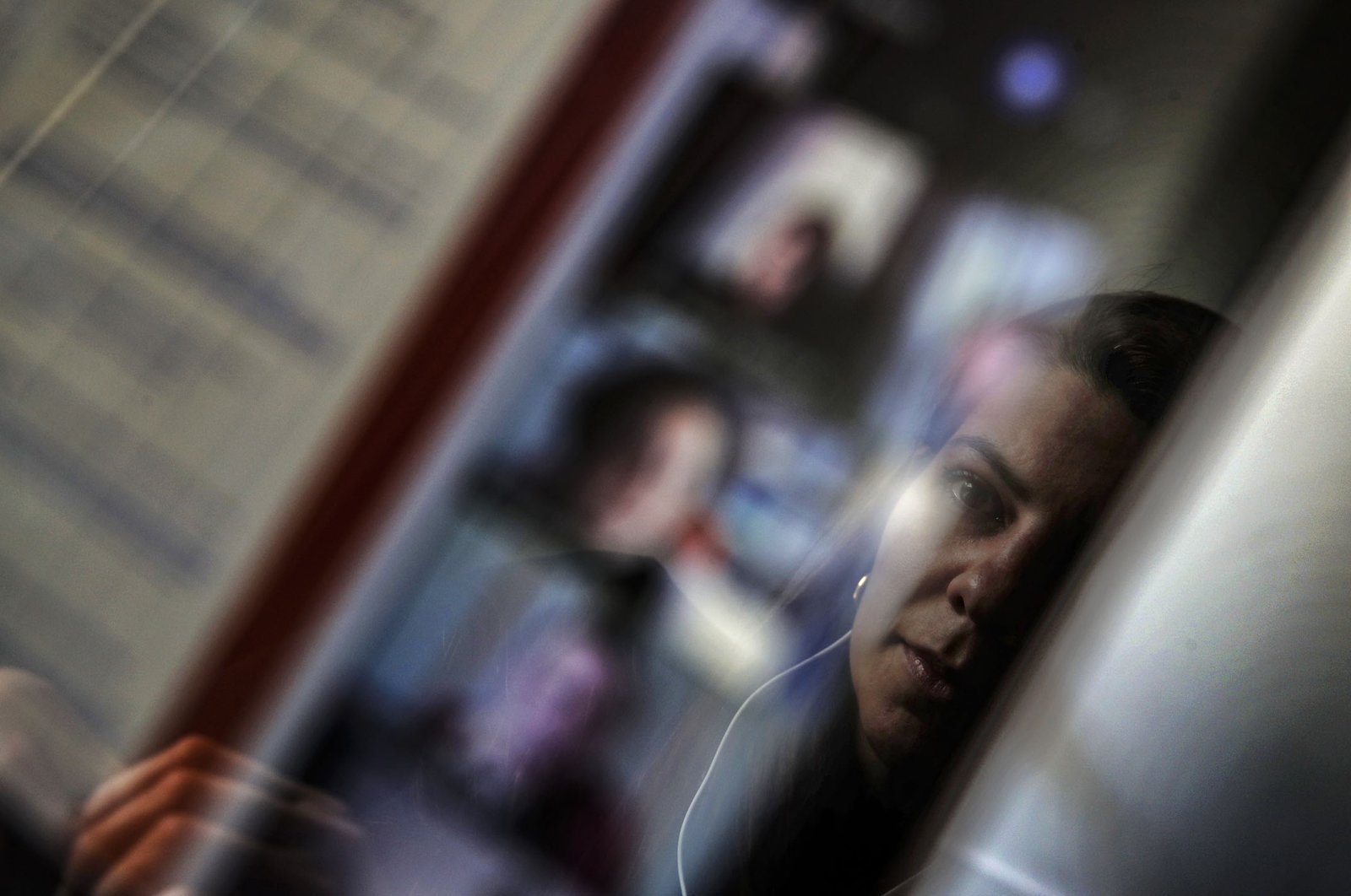 A student studying the psychiatry of old people is reflected in the screen of her computer as she attends a remote course at her student housing, in Ivry sur Seine, outside Paris, France, Feb. 11, 2021.  (AP Photo)