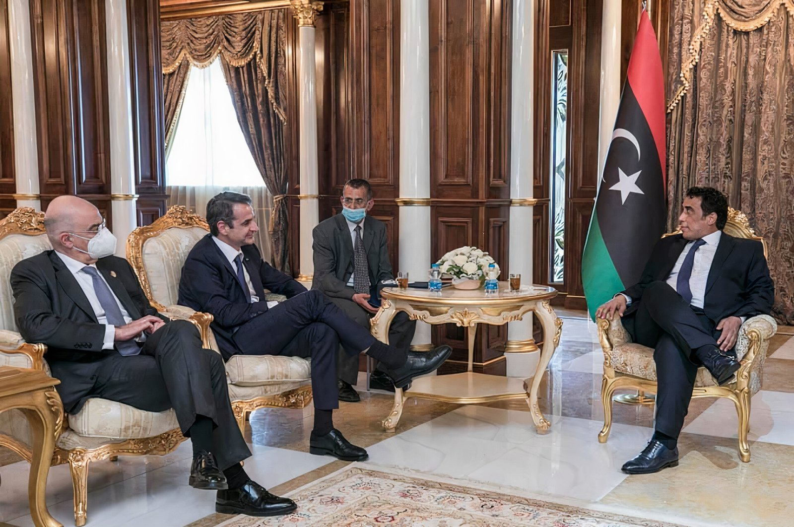 Libya's current head of the Presidential Council, Mohammad Younes Menfi, who had served for almost a year as Libya's ambassador in Greece (R) hosts Greece's Prime Minister Kyriakos Mitsotakis and the Greek Foreign Minister Nikos Dendias in the Libyan capital Tripoli on April 6, 2021. (Photo taken from Menfi's personal Facebook page)