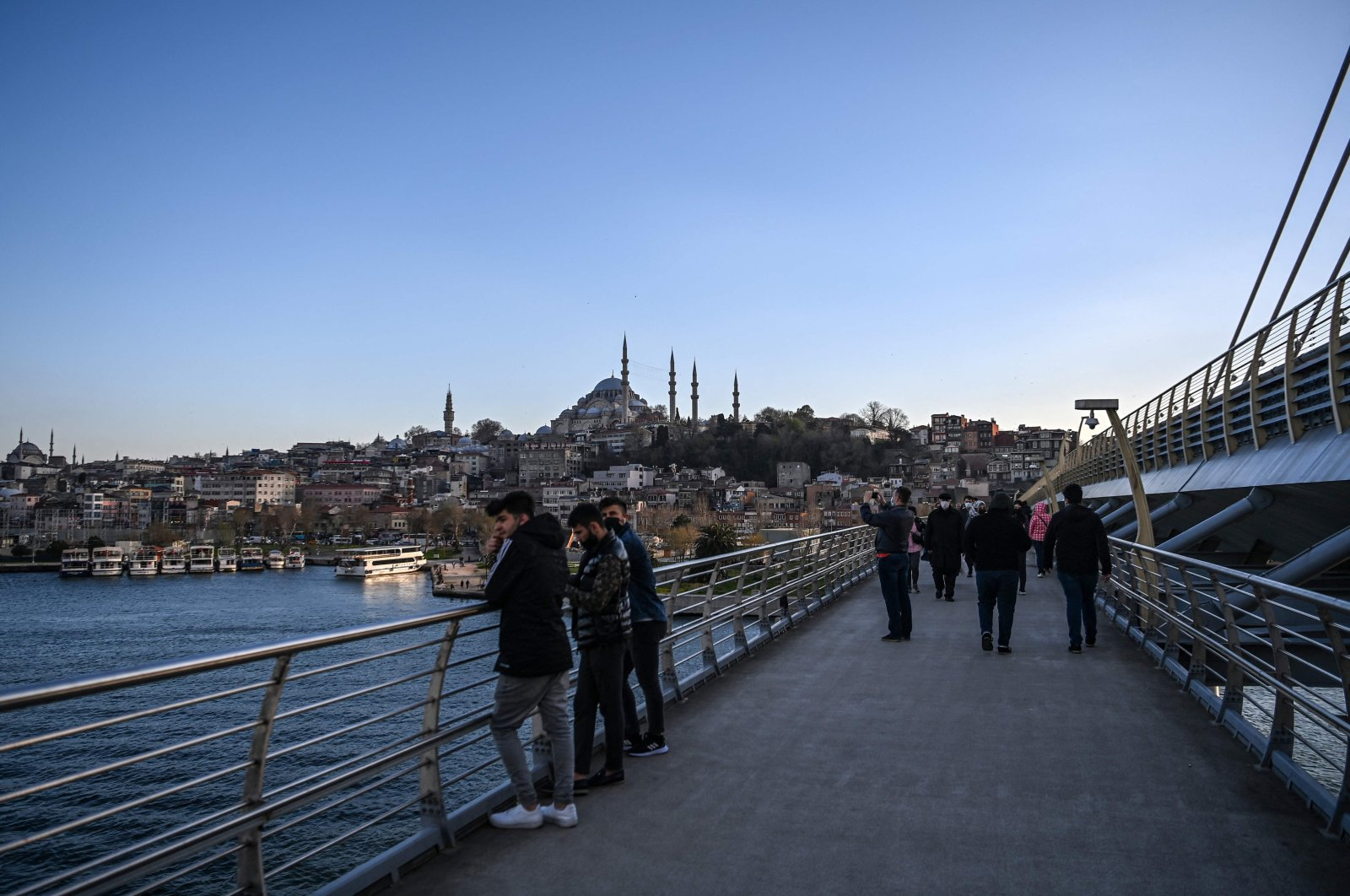 People walk on the metro bridge, with the Süleymaniye Mosque in the background, in the Karakoy neighborhood of Istanbul, Turkey, April 7, 2021. (AFP Photo)
