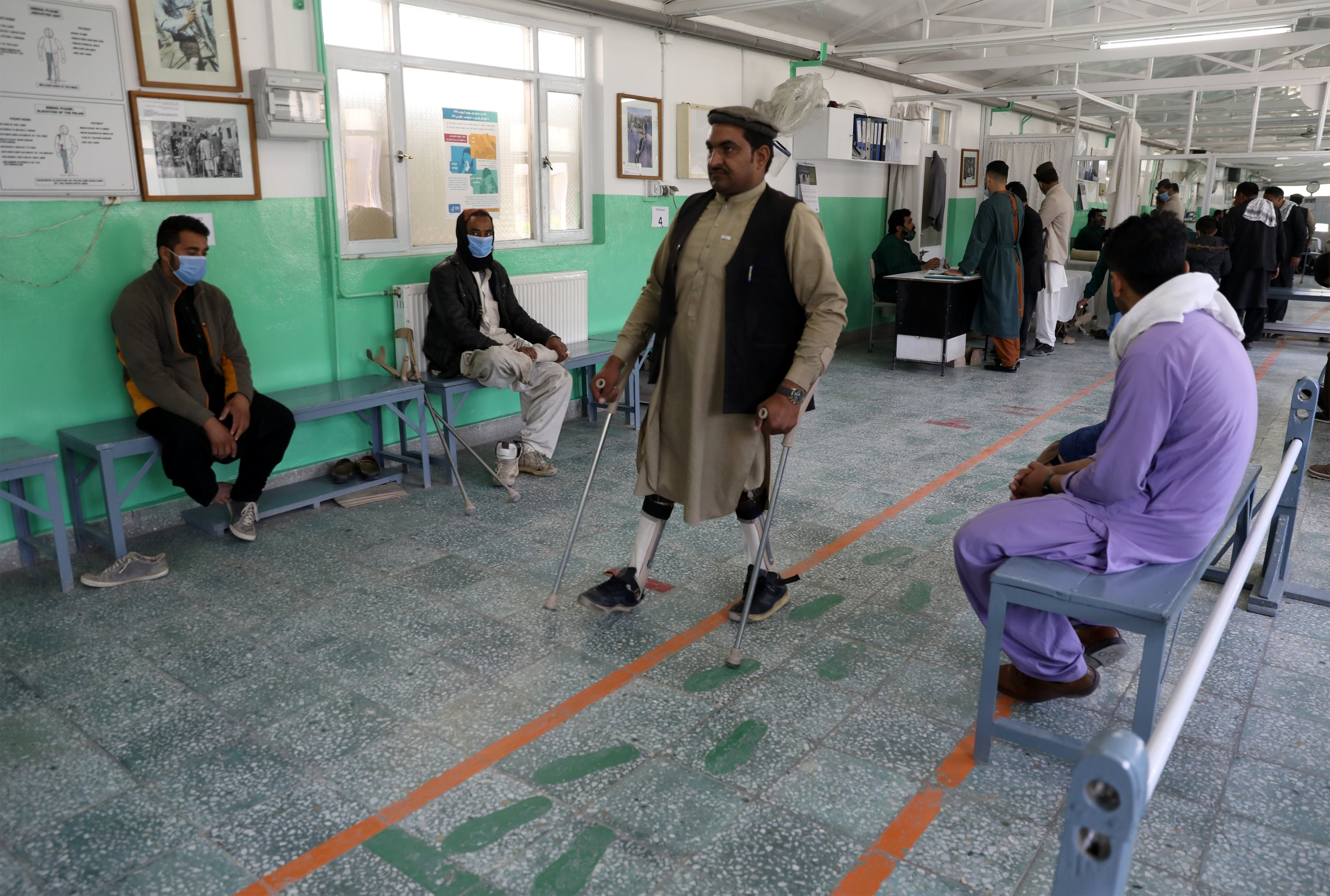 Afghan polio patient Maiwa Gul tests his new orthopedic devices at the International Committee of the Red Cross' Orthopedic Program, in Kabul, Afghanistan, March 29, 2021. (AP Photo)