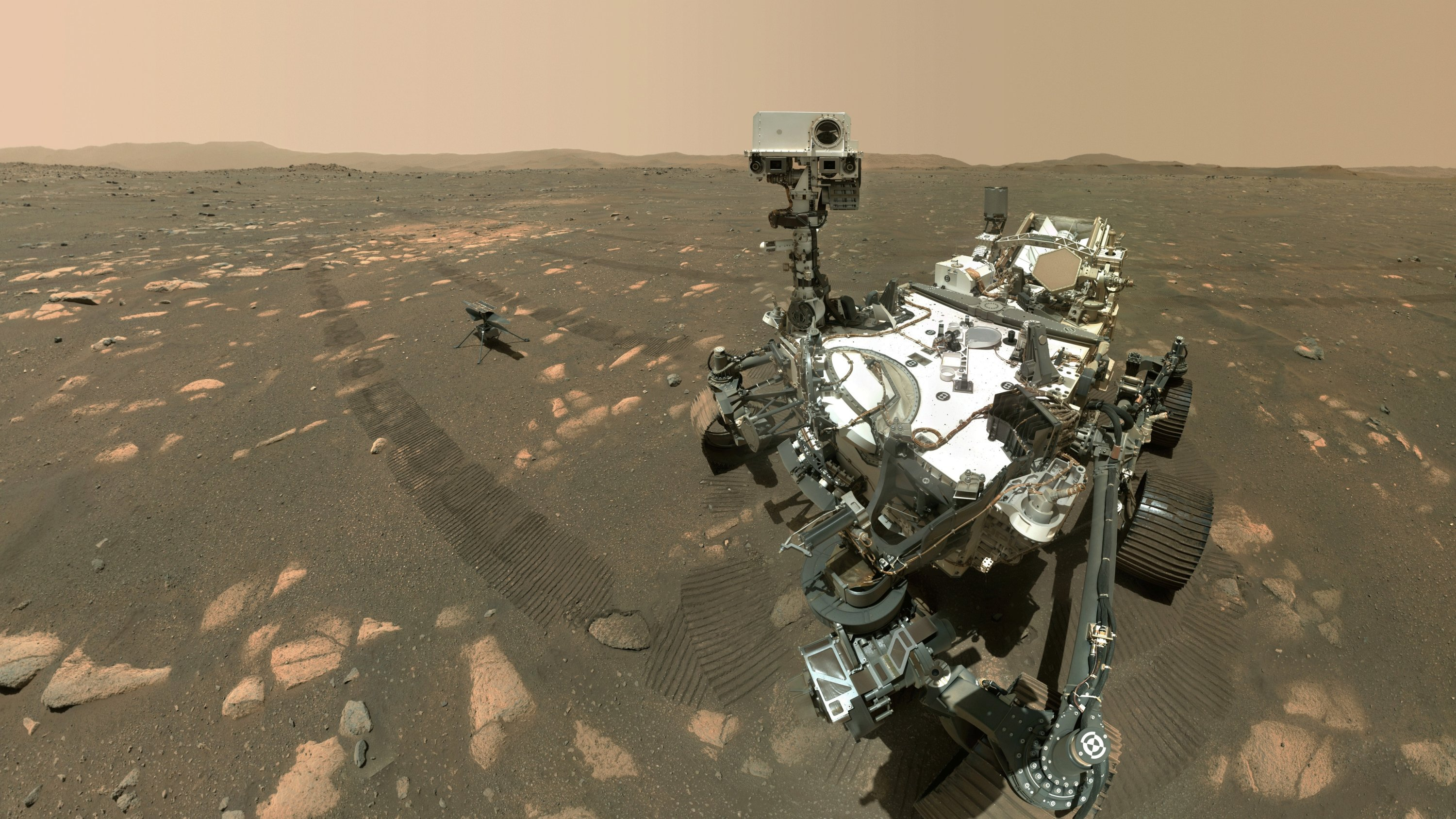 The Perseverance Mars rover (front) and the Ingenuity helicopter about 13 feet (3.9 meters) behind. This composite image was made by the WASTON camera on the rover's robotic arm on the 46th Martian day, or sol, of the mission, or April 6, 2021. (NASA/JPL-Caltech/MSSS via AP)