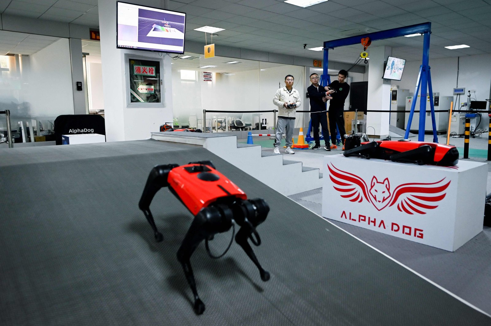 An engineer (background R) controlling an AlphaDog quadruped robot in a workshop at the Weilan Intelligent Technology Corporation in Nanjing, China's Jiangsu province, April 2, 2021. (AFP Photo)
