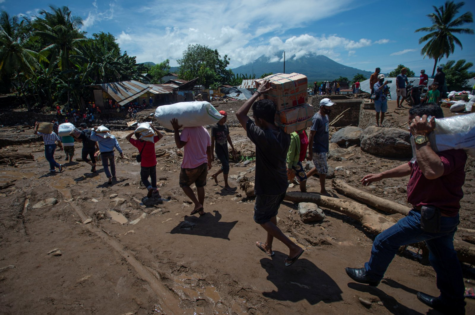 People carry relief supplies following flash floods triggered by tropical cyclone Seroja in East Flores, East Nusa Tenggara province, Indonesia, April 7, 2021. (Antara Foto via Reuters)
