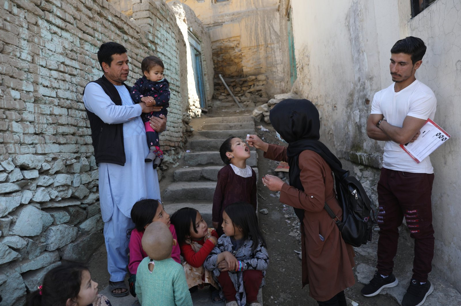 Shabana Maani, a volunteer polio vaccinator, gives a polio vaccination to a child in the old part of Kabul, Afghanistan, March 29, 2021. (AP Photo)