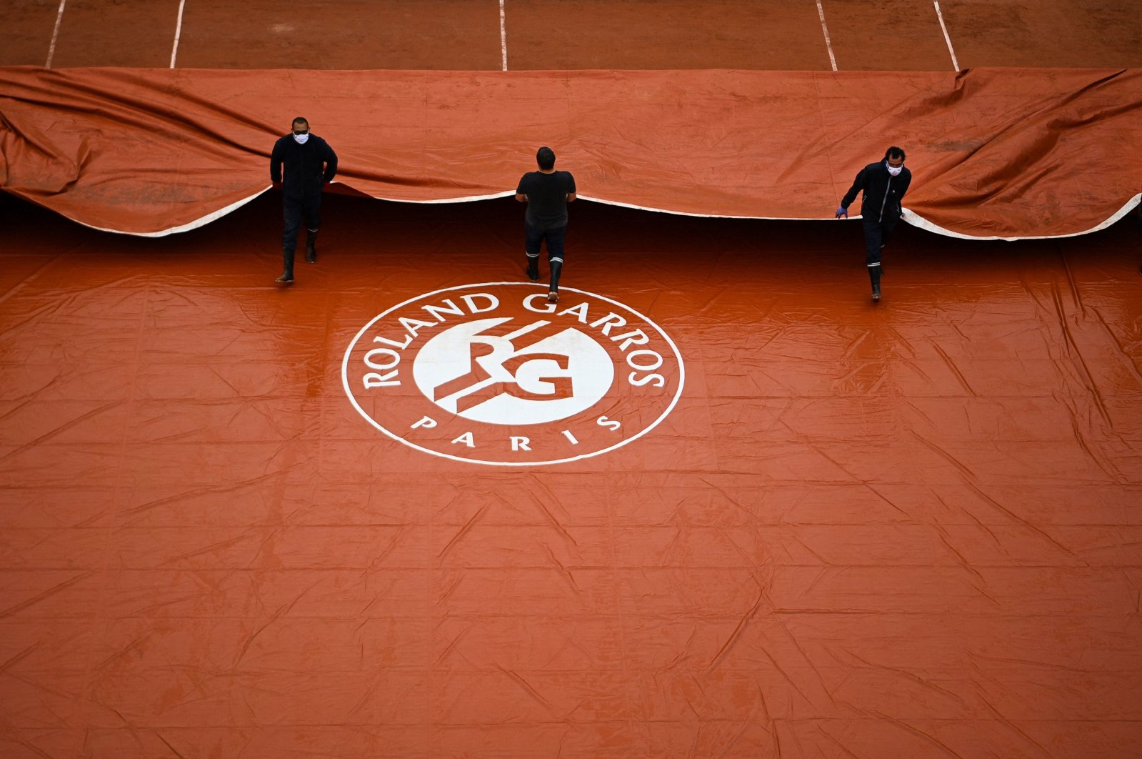 Ground staff members take off the cover across the Suzanne Lenglen court at The Roland Garros 2020 French Open in Paris, France, Sept. 28, 2020. (AFP Photo)