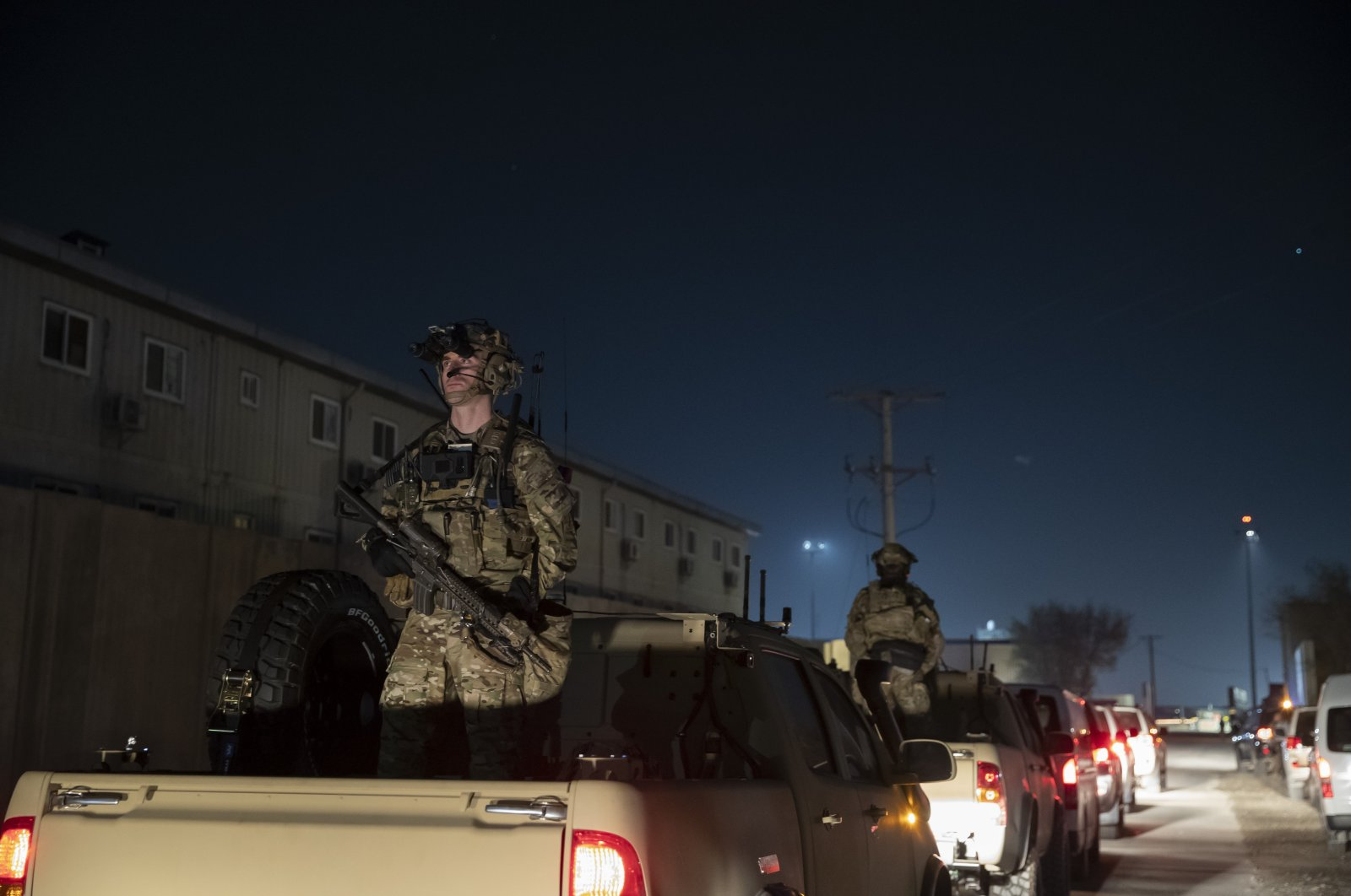 Armed soldiers stand guard in the motorcade for President Donald Trump as he speaks during a surprise Thanksgiving Day visit to the troops at Bagram Air Field, Afghanistan, Nov. 28, 2019. (AP Photo)
