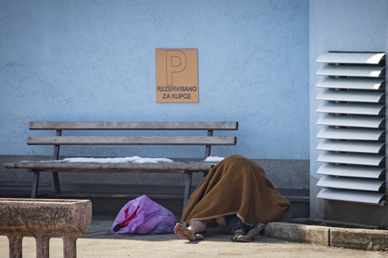 A migrant sits on the pavement to warm up outside the Miral camp, in Velika Kladusa, Bosnia-Herzegovina, April 7, 2021. (AP Photo)