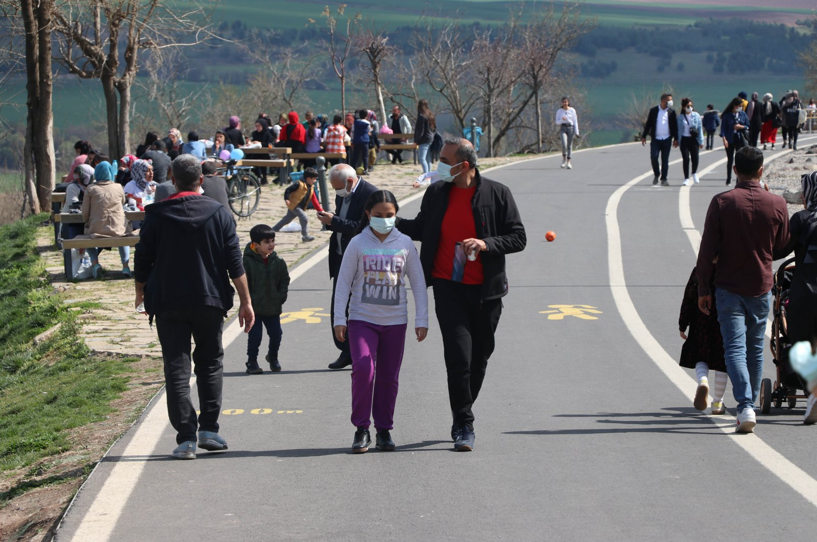 People wearing protective masks walk in a park in Diyarbakır, southeastern Turkey, April 8, 2021. (DHA PHOTO)