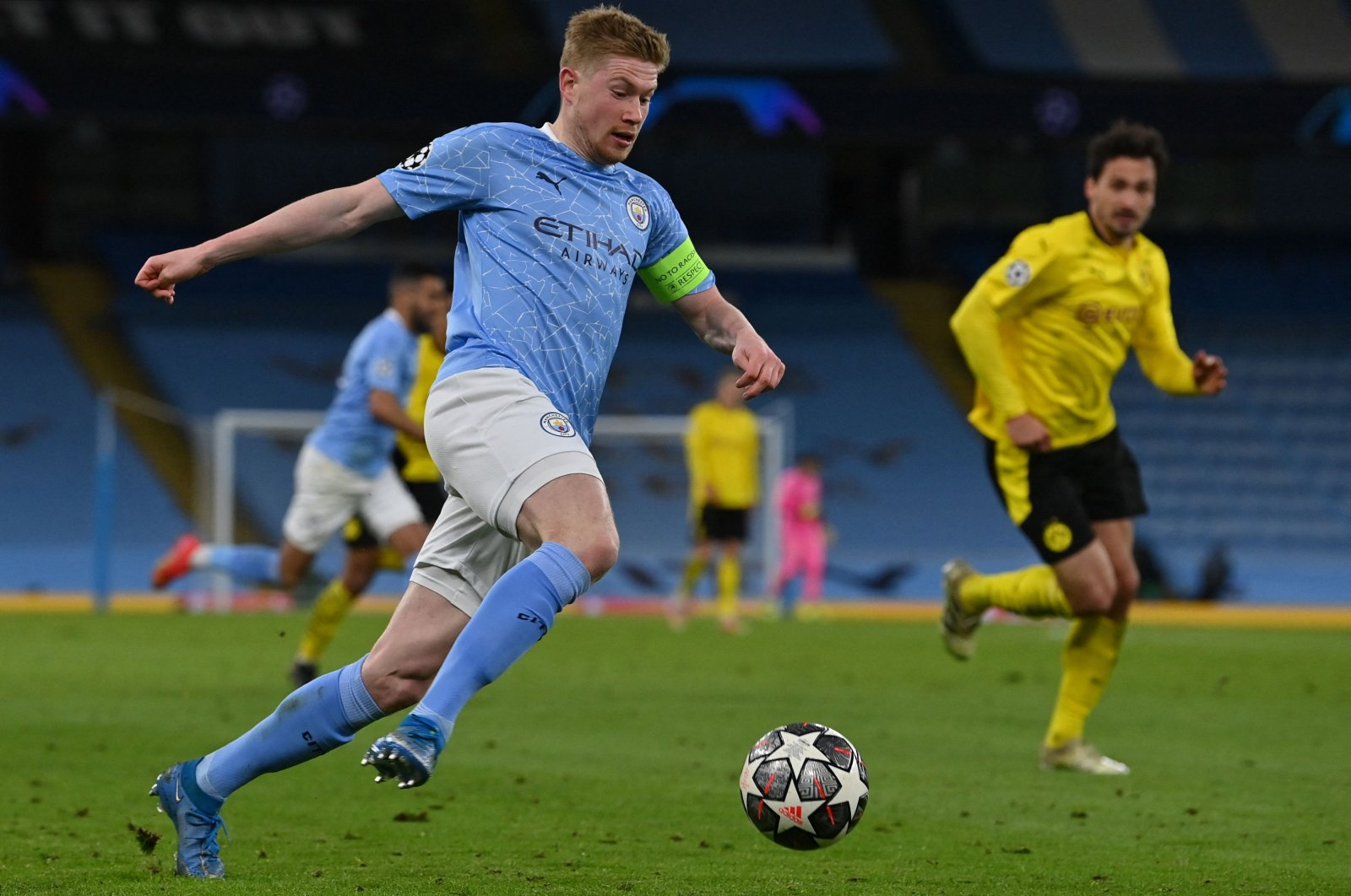 Manchester City's Belgian midfielder Kevin De Bruyne (L) runs with the ball during the UEFA Champions League first-leg, quarterfinal match against Borussia Dortmund at the Etihad Stadium, in Manchester, England, April 6, 2021. (AFP Photo)