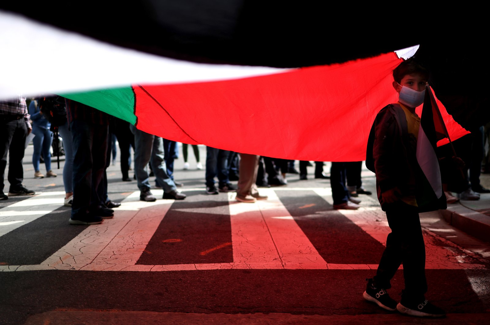 A young boy stands beneath a Palestinian flag as protesters from multiple Palestinian rights organizations demonstrate outside the White House, Washington, D.C., U.S., Sept. 15, 2020. (Photo by Getty Images)