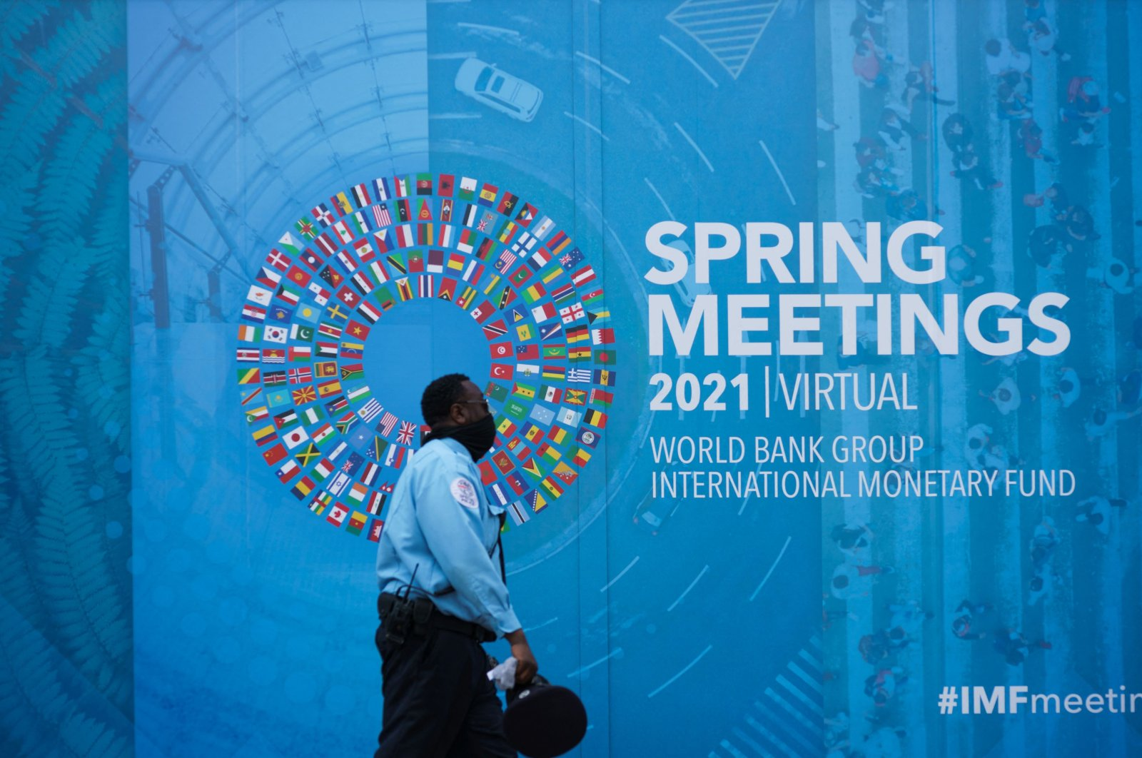 People pass by a banner for the World Bank Group/International Monetary Fund Virtual Spring Meetings in Washington, D.C., the U.S., April 7, 2021. (AFP Photo)