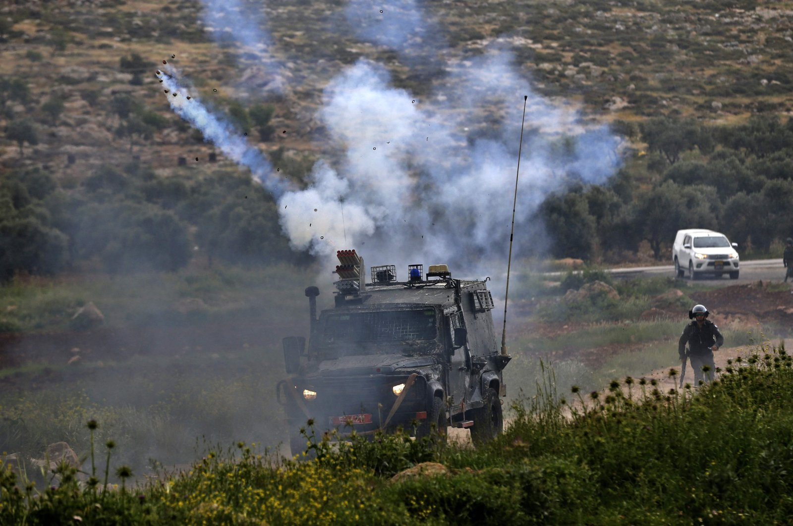 Tear gas is fired by Israeli forces against Palestinian protesters during clashes in the village of al-Mughayer near the Israeli-occupied West Bank city of Ramallah, April 2, 2021. (AFP Photo)