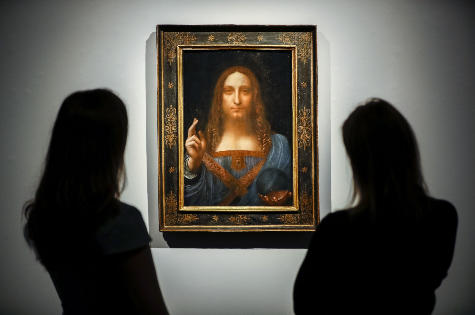 "Christie's employees pose in front of a painting entitled ""Salvator Mundi"" at a photocall at Christie's auction house in central London, U.K., Oct. 22, 2017, ahead of its sale at Christie's New York on Nov. 15, 2017. (AFP Photo)"