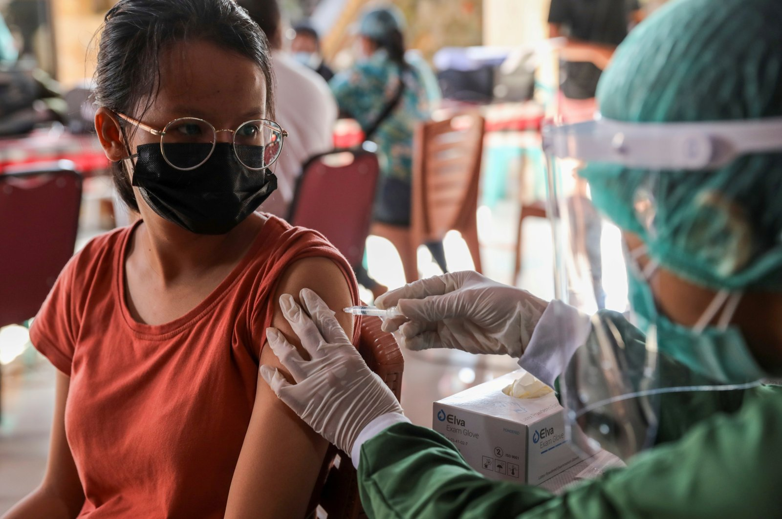A woman receives a dose of AstraZeneca coronavirus disease vaccine during a mass vaccination program for Green Zone Tourism in Sanur, Bali, Indonesia, March 23, 2021. (Reuters Photo)