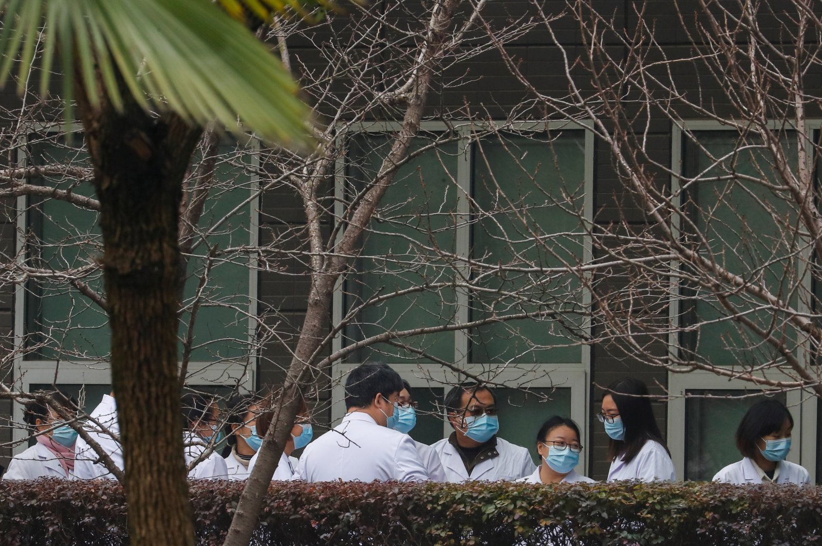 Chinese scientists and officials in lab coats wait at the Hubei Animal Epidemic Disease Prevention and Control Center during a visit of a team of the World Health Organization (WHO), tasked with investigating the origins of the coronavirus disease (COVID-19), in Wuhan, Hubei province, China, Feb. 2, 2021. (Reuters Photo)