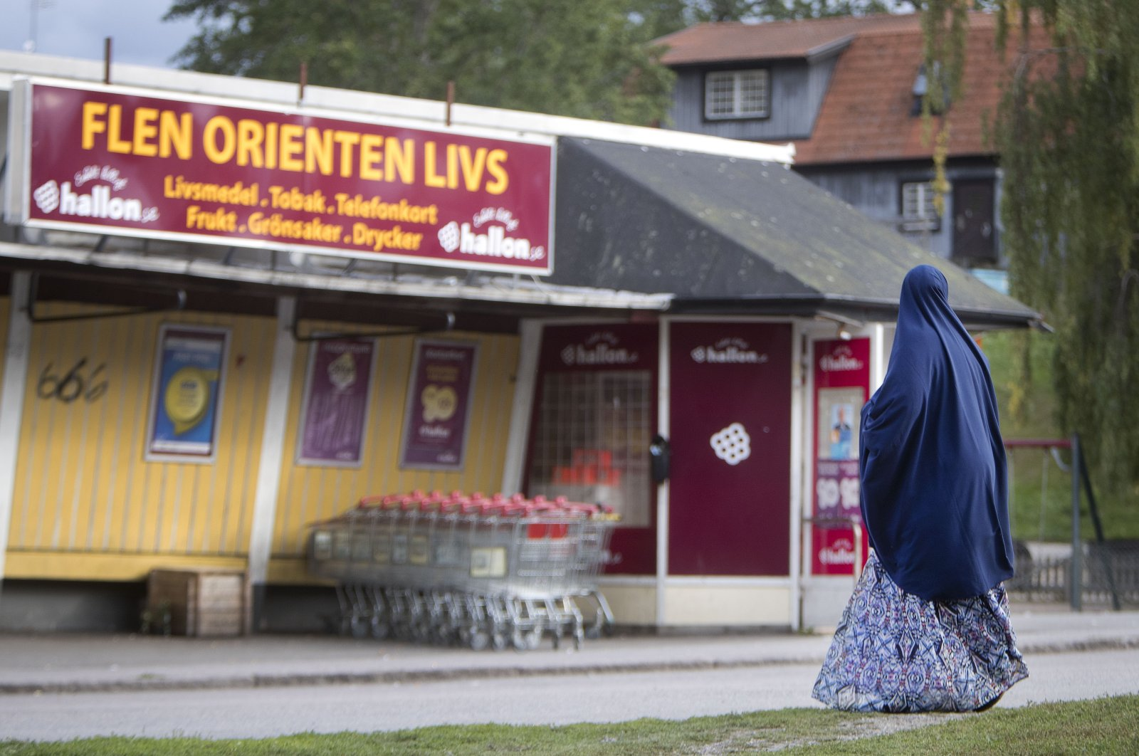 A migrant woman stands in front of an orient supermarket in Flen, some 100 km west of Stockholm, Sweden, Aug. 30, 2018. (AP File Photo)