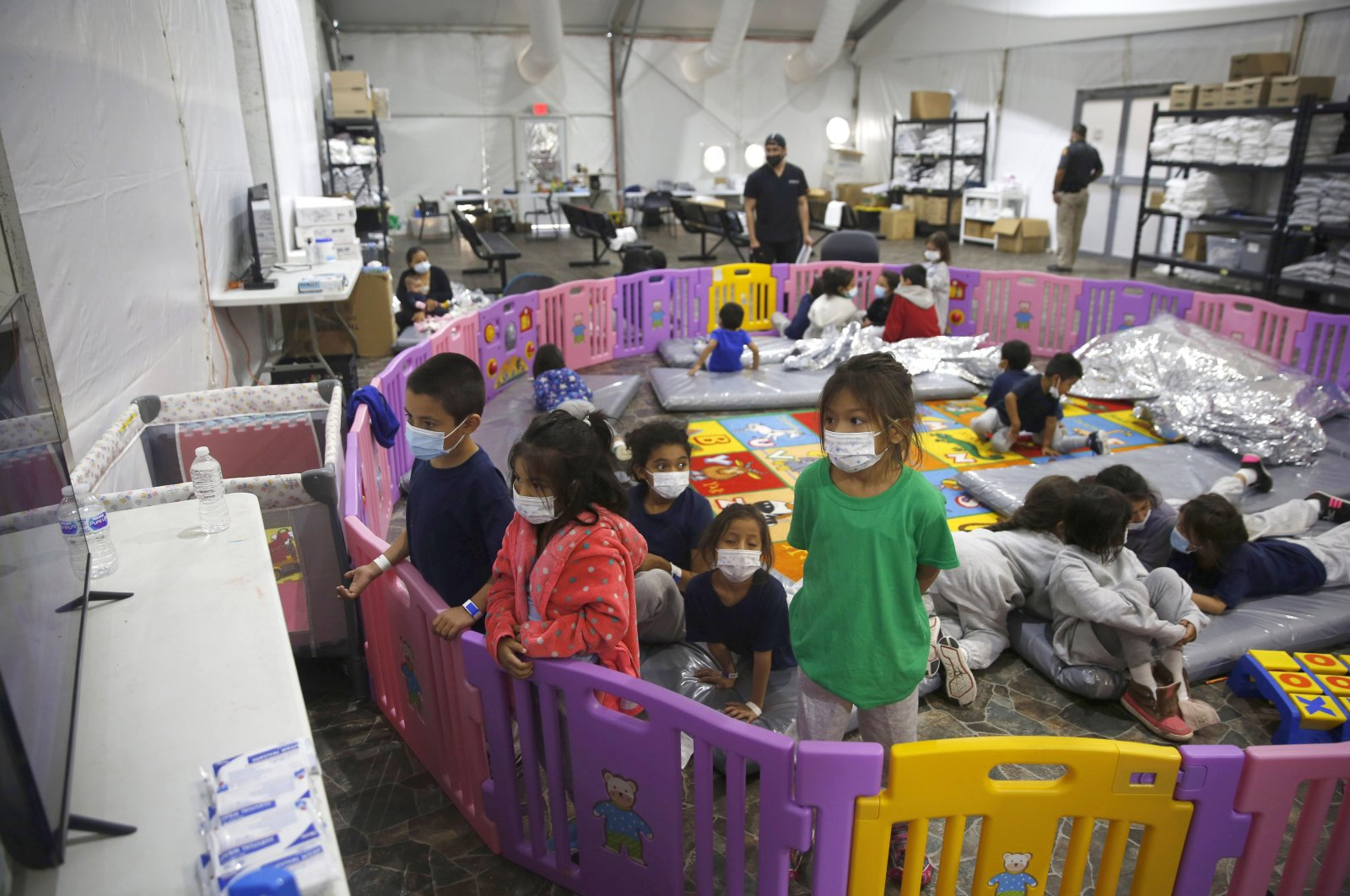 Young unaccompanied migrants, from ages 3 to 9, watch television inside a playpen at the U.S. Customs and Border Protection facility, the main detention center for unaccompanied children in the Rio Grande Valley, in Donna, Texas. U.S, on March 30, 2021. (AP Photo)