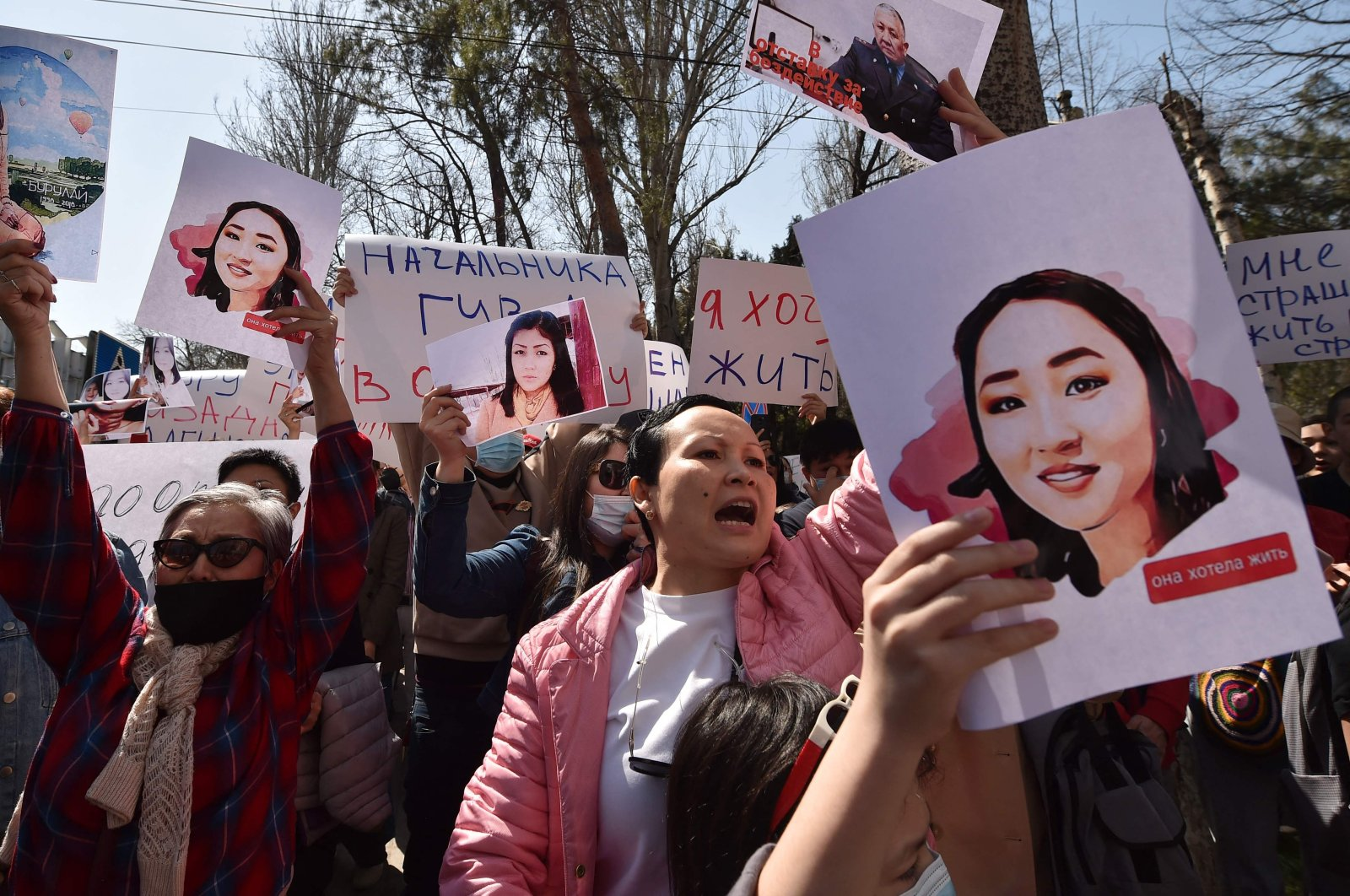 People hold pictures as they attend a rally for the protection of women's rights in Bishkek, Kyrgyzstan, on April 8, 2021. (AFP Photo)
