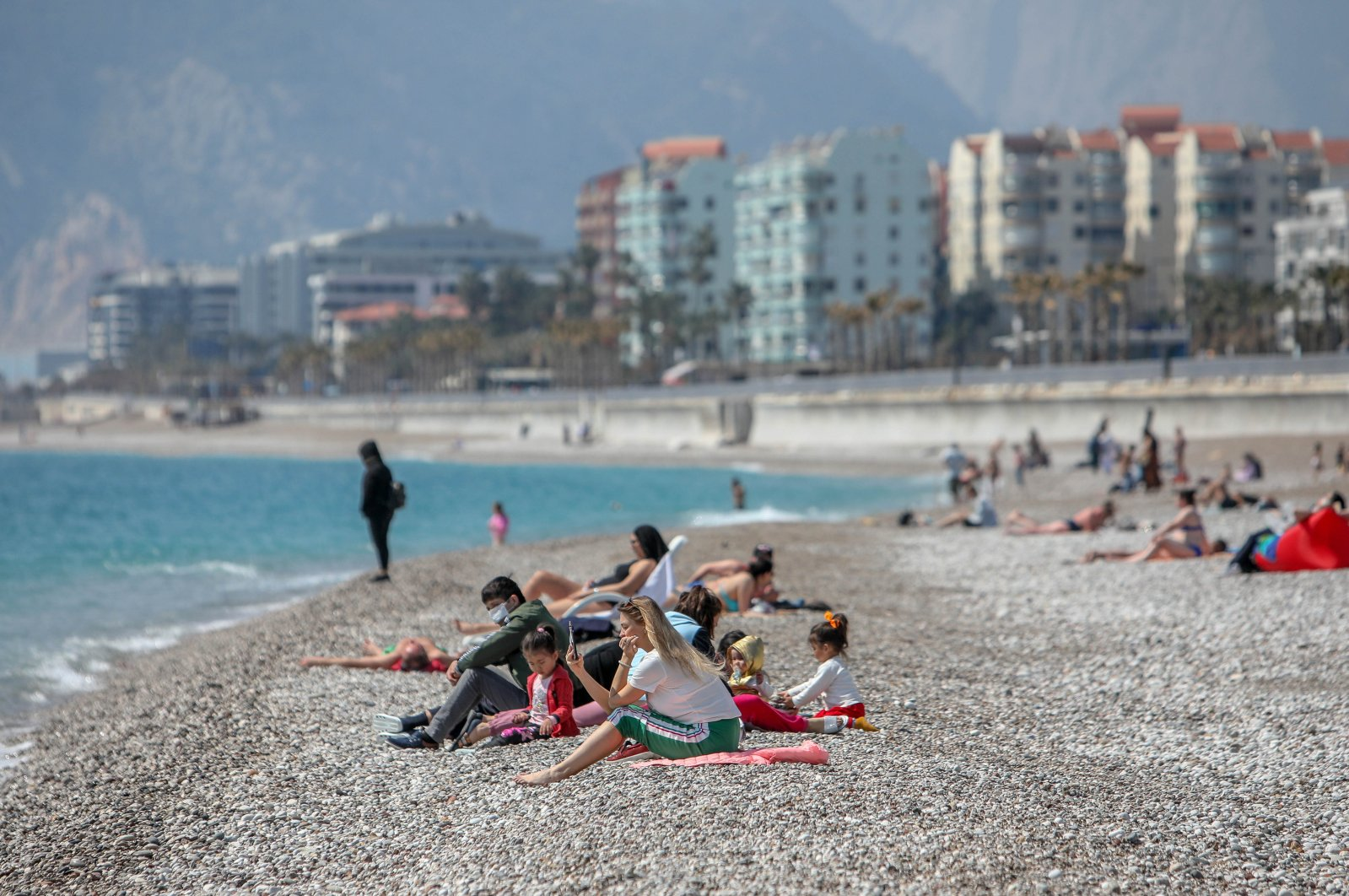 People on a beach in the Mediterranean resort province Antalya, southern Turkey, April 3, 2021. (DHA Photo)