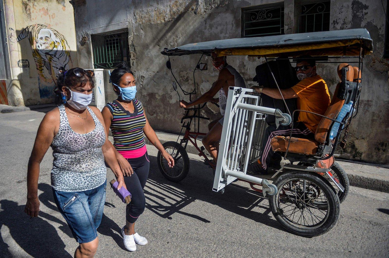 Women wearing masks walk along along a street. Havana, Cuba, on April 6, 2021. (AFP Photo)