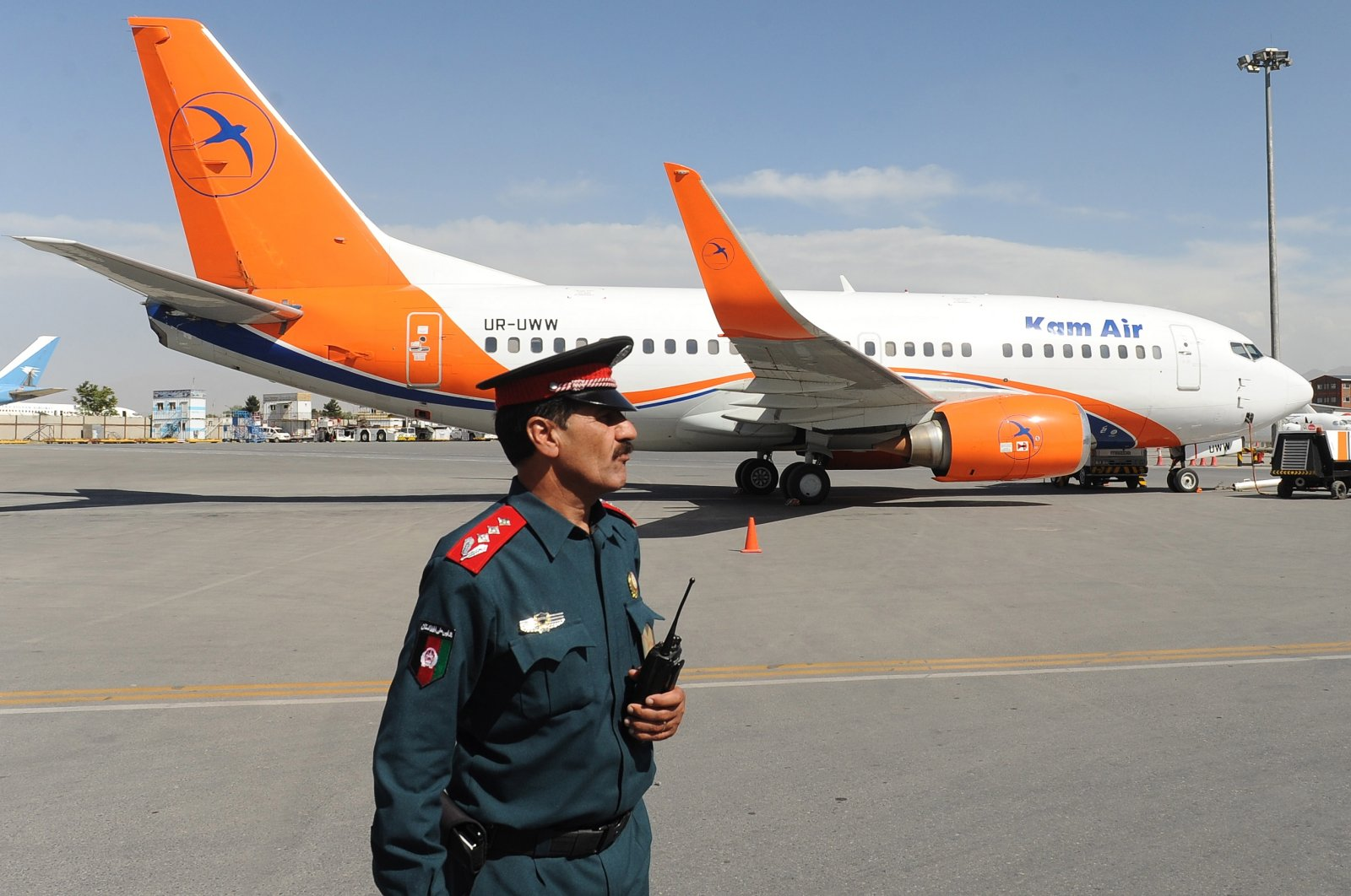An Afghan police officer stands guard in front of a Boeing 737-500 of Afghan carrier Kam Air at the Kabul International Airport in Kabul, Afghanistan, on June 26, 2018. (EPA Photos)