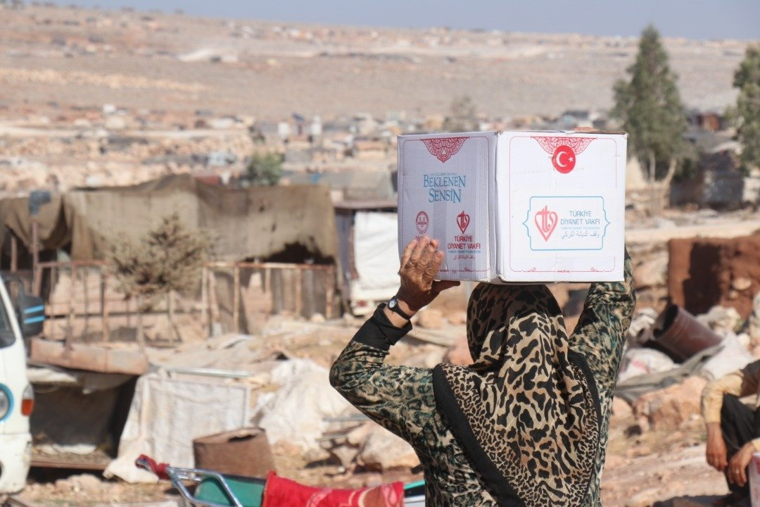 A Syrian woman carries an aid package distributed by the Türkiye Diyanet Foundation (TDV) in Idlib, Syria, Sept. 9, 2019. (Sabah File Photo)