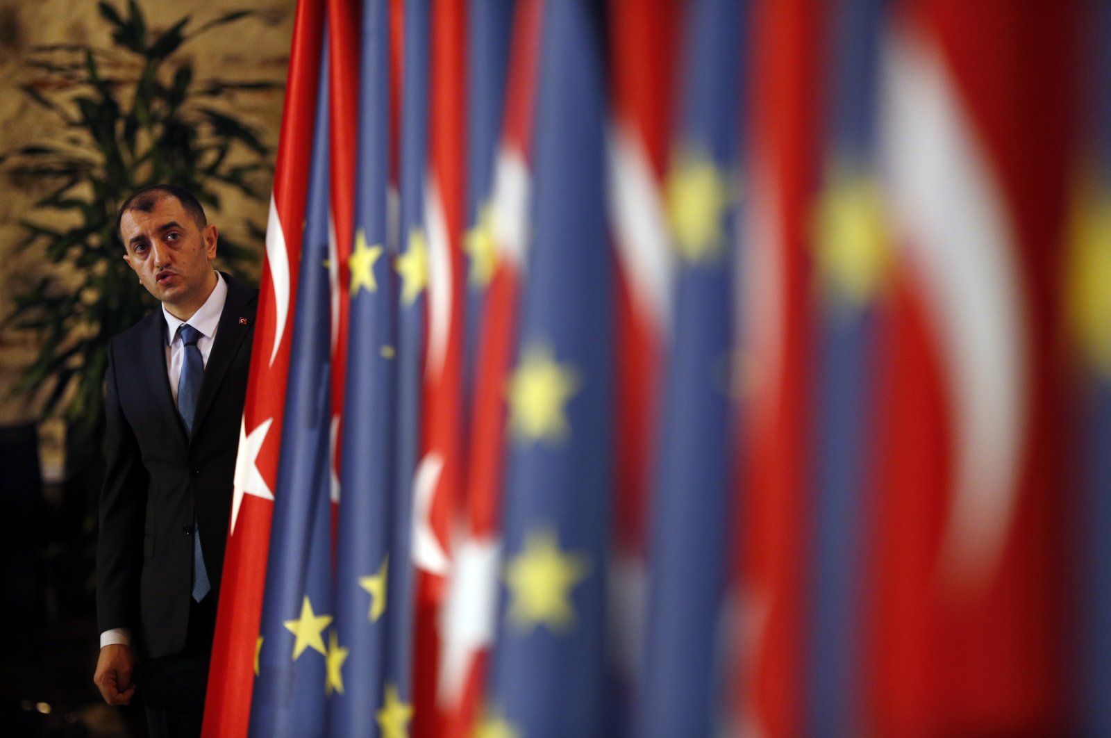 An official helps adjust the flags of Turkey and the European Union prior to the opening session of a high-level meeting the two sides, in Istanbul, Turkey, Thursday, Feb. 28, 2019. (AP File Photo)