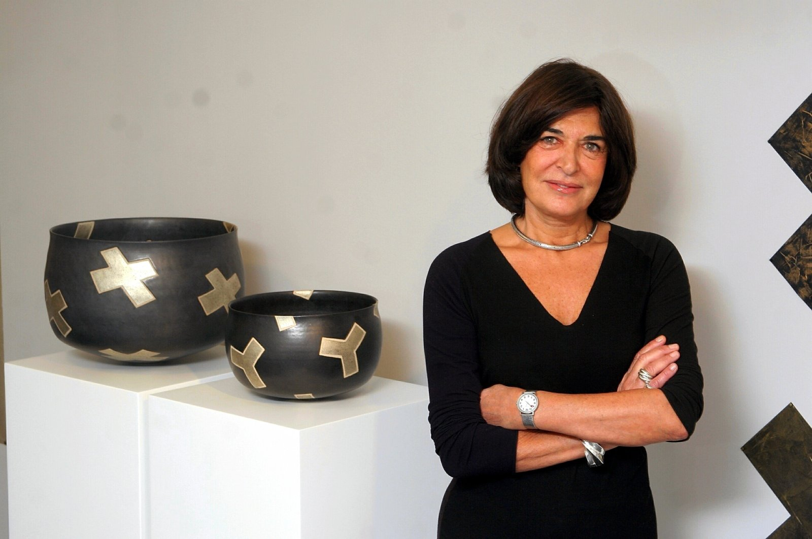 Alev Ebuziyya Siesbye poses with two of her ceramic works at one of her previous exhibitions at Gallery Nev in Istanbul, Turkey. (Sabah Photo)