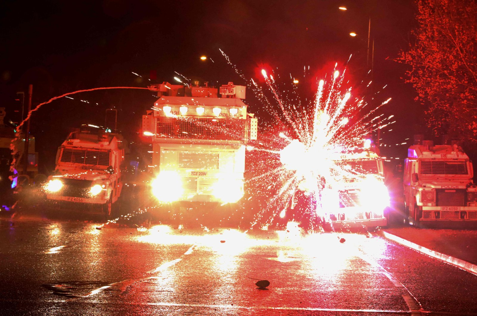 Fireworks explode at police vehicles after being fired at police officers with a water cannon during clashes with nationalist youths in the Springfield Road area as disorder continued in the Northern Ireland capital following days of mainly loyalist violence, Belfast, North Ireland, April 8, 2021. (AFP Photo)