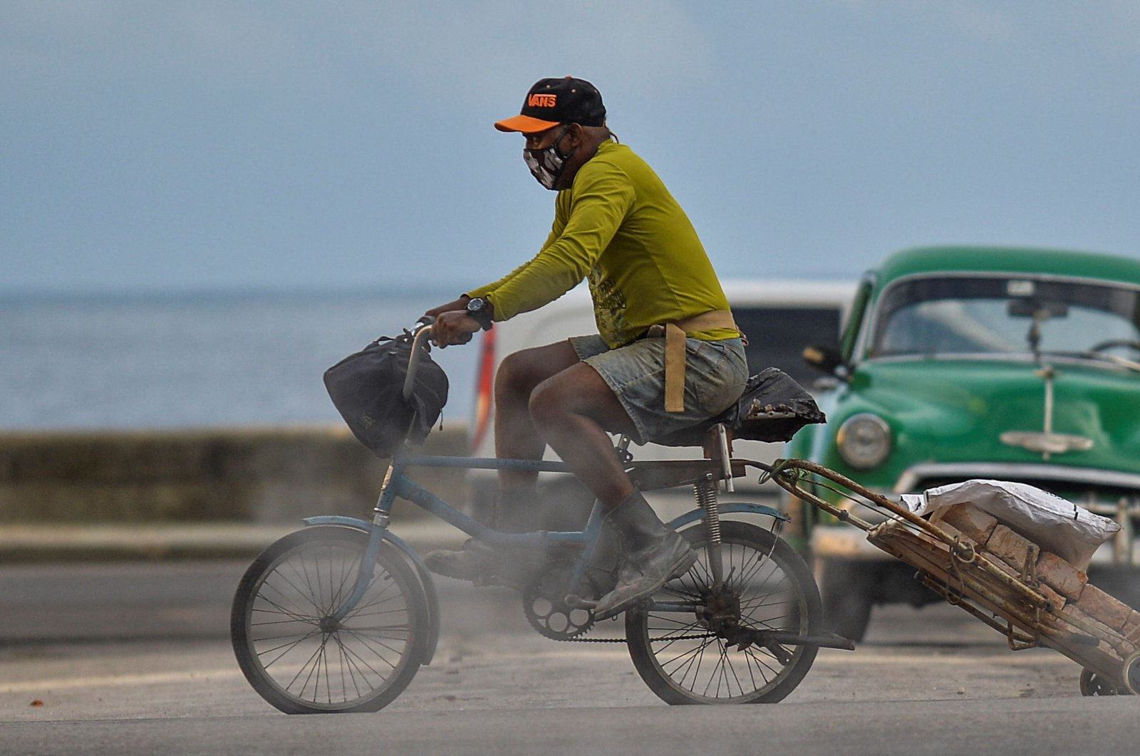 A man wearing a face mask transports bricks on his bicycle along a street of Havana, Cuba, April 6, 2021. (AFP Photo)