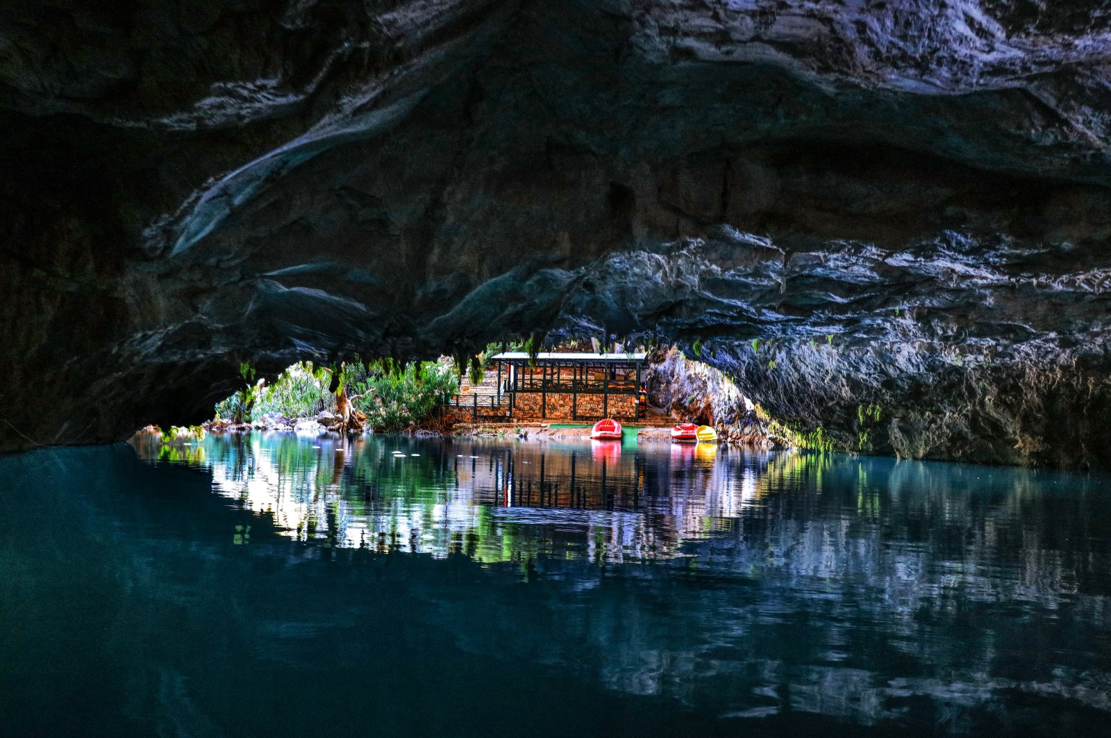 The entrance to Altınbeşik Cave and its lake with its clear, pristine waters and a wooden hut in the background, Antalya, southern Turkey. (AA Photo)