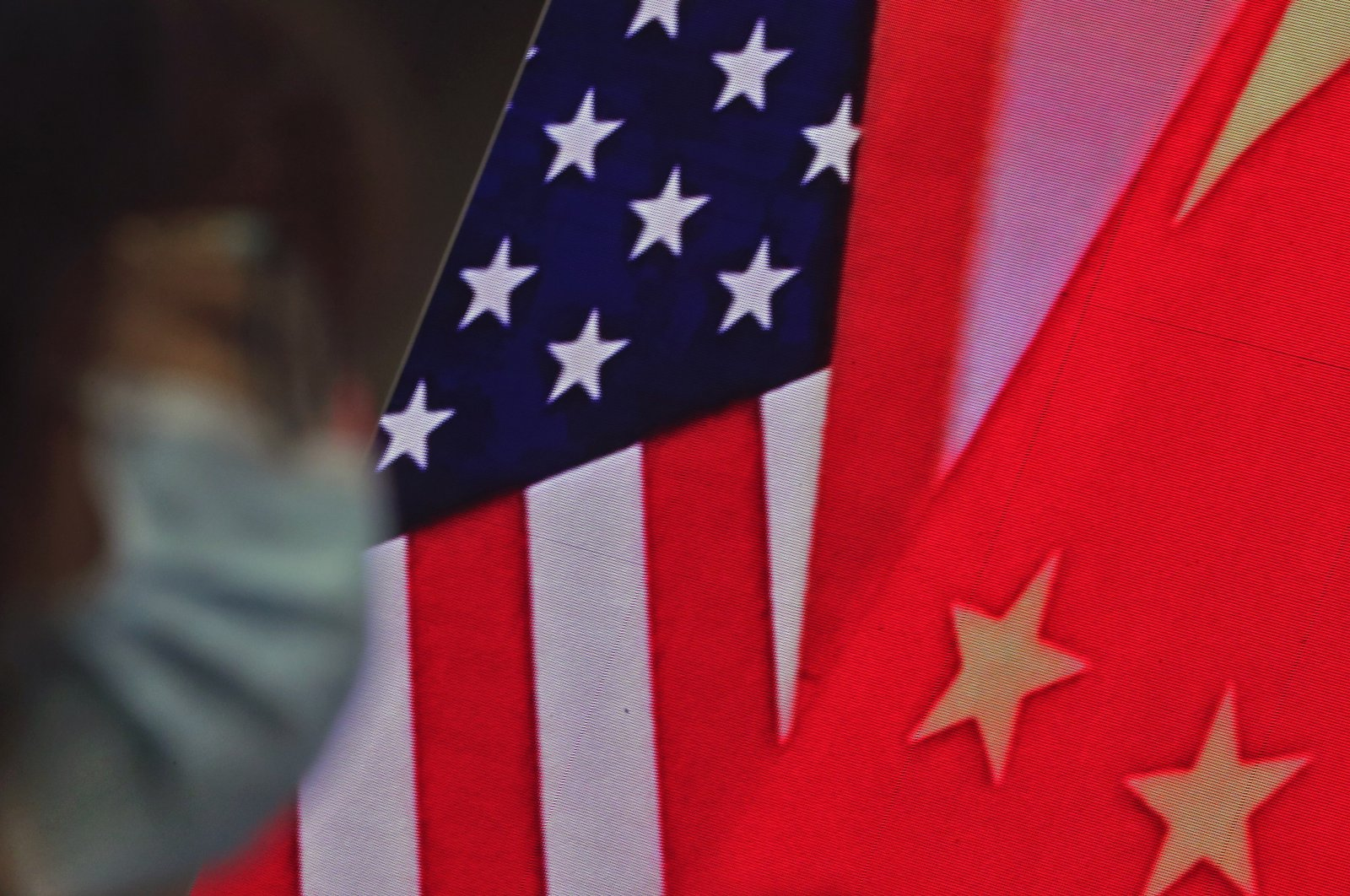 A woman wearing a face mask sits near a screen showing China and U.S. flags at the Ministry of Foreign Affairs office in Beijing, China, Feb. 22, 2021. (AP Photo)