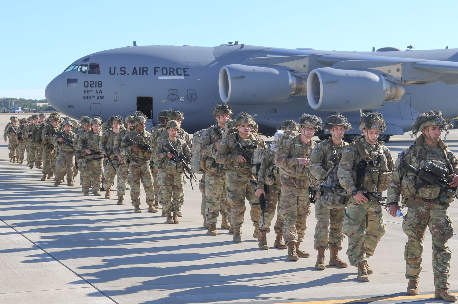 This handout picture released by the US Army shows U.S. Army Paratroopers assigned to the 2nd Battalion, 504th Parachute Infantry Regiment, 1st Brigade Combat Team, 82nd Airborne Division, deploy from Pope Army Airfield, North Carolina, U.S., Jan. 1, 2020. (US Army via AFP)
